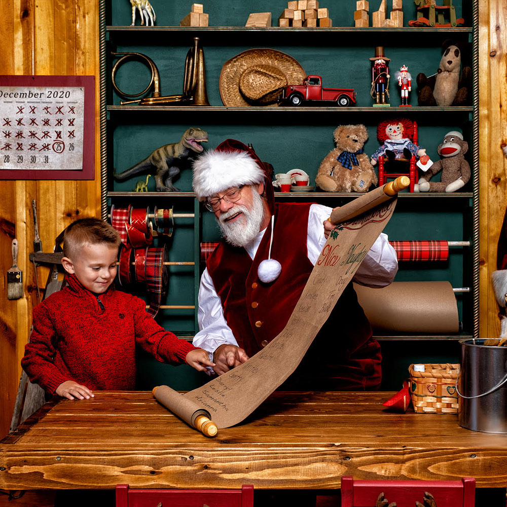 little boy with Santa in Santa's workshop